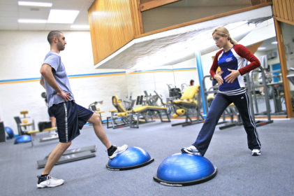 1024px-Personal_trainer_showing_a_client_how_to_exercise_the_right_way_and_educating_them_along_the_way